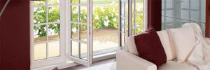 Salon d'une maison avec un canapé et des fenêtres blanches en PVC