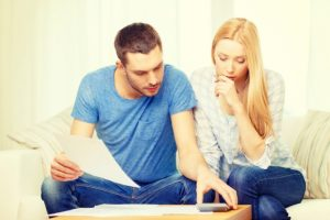 Couple entrain de faire des calculs dans leur salon